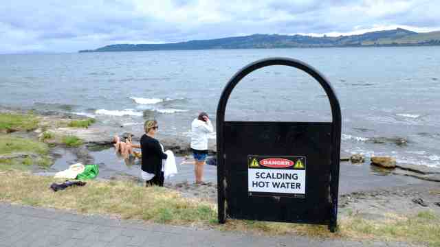 Sign warning of scalding water, people on lakeside enjoying a hot spa Lake Taupo