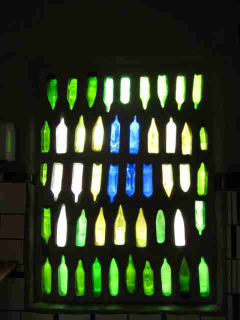Colourful bottles set into brickwork